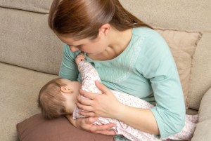Young mother breast feeding her baby